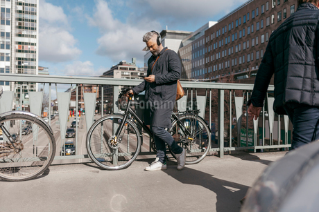 Man with bicycle and smart phone on street in Stockholm, Swedenの写真素材 [FYI02208572]