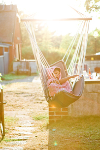 Girl in hammock at sunset in Friseboda, Swedenの写真素材 [FYI02208582]