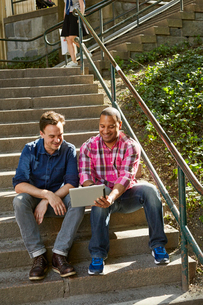 Sweden, Mature men sitting side by side on steps and looking at digital tabletの写真素材 [FYI02208606]