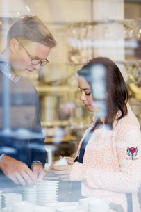 Sweden, Young couple choosing porcelain bowls in shopの写真素材 [FYI02208624]