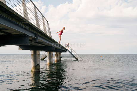 Sweden, Skane, Malmo, Woman jumping into water from pierの写真素材 [FYI02208629]