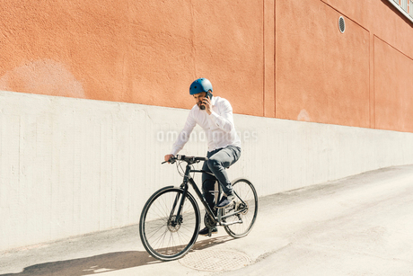 Man on smart phone while bicycling in Swedenの写真素材 [FYI02208630]