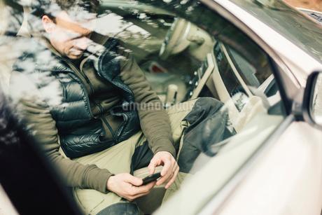 Man on smart phone behind car window in Swedenの写真素材 [FYI02208637]
