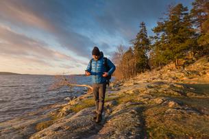 Man walking along coastline in Jarfalla, Swedenの写真素材 [FYI02208643]