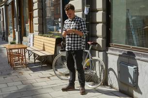 Sweden, Stockholm, Man texting on sidewalkの写真素材 [FYI02208686]