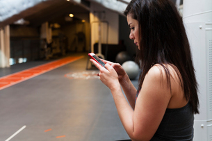 Sweden, Young woman texting at gymの写真素材 [FYI02208687]