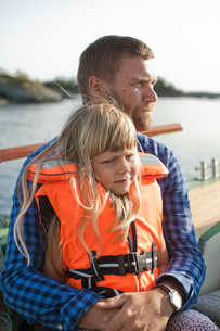 Norway, Bergen, Girl (4-5) in life jacket sitting on father´s lapsの写真素材 [FYI02208712]