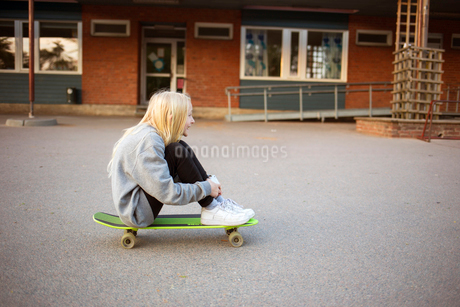 Sweden, Vastergotland, Lerum, Girl (12-13) sitting on skateboardの写真素材 [FYI02208719]