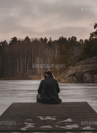 Rear view of man on wharf at Lake Flaten in Skarpnack, Swedenの写真素材 [FYI02208757]