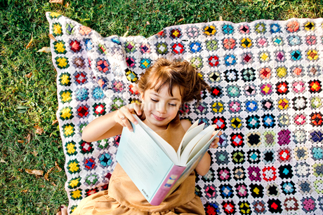 Girl reading on picnic blanket in Friseboda, Swedenの写真素材 [FYI02208764]