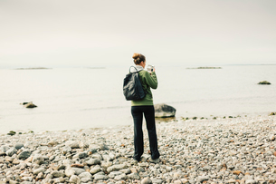 Rear view of woman on rocky coastline in Sodermanland, Swedenの写真素材 [FYI02208765]