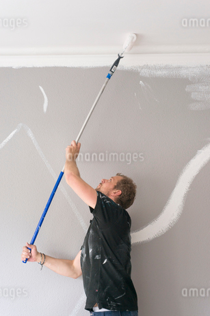Sweden, Man painting ceiling in roomの写真素材 [FYI02208774]