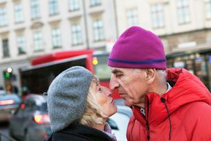 Sweden, Stockholm, Sodermalm, Senior couple kissing in streetの写真素材 [FYI02208783]
