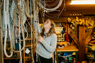 Teenage girl reaching up to touch ropes in rope maker storeの写真素材 [FYI02208805]