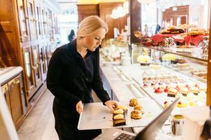 Baker putting baked goods in display window in Swedenの写真素材 [FYI02208810]