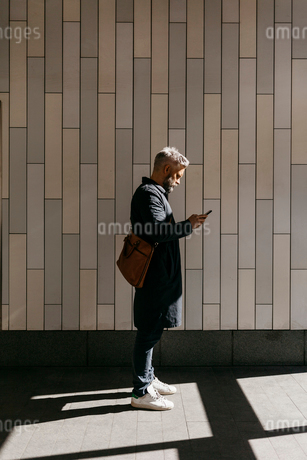 Man texting on street in Stockholm, Swedenの写真素材 [FYI02208815]