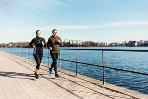Man and woman running along street in Stockholm, Swedenの写真素材 [FYI02208828]