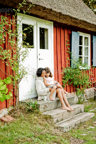 Mother and daughter sitting on steps in Friseboda, Swedenの写真素材 [FYI02208850]