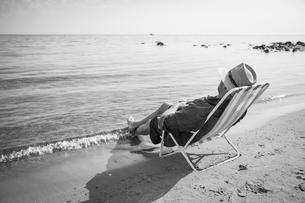 Sweden, Gotland, Mature man sitting on deckchair at seashoreの写真素材 [FYI02208859]