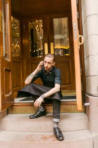 Baker on steps outside bakery in Swedenの写真素材 [FYI02208867]
