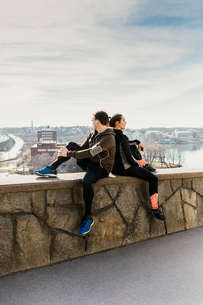 Couple sitting on stone wall in Stockholm, Swedenの写真素材 [FYI02208879]