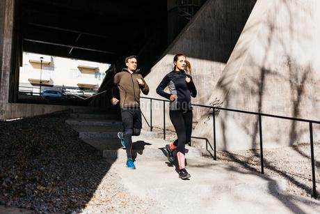 Couple running on street in Stockholm, Swedenの写真素材 [FYI02208902]