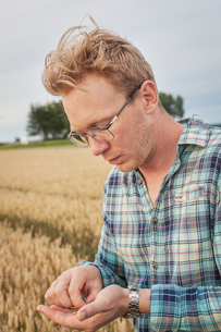 Finland, Uusimaa, Siuntio, Mid adult man holding wheat grainの写真素材 [FYI02208915]