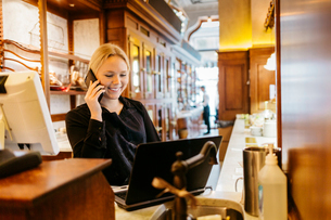 Waitress at bakery on phone in Swedenの写真素材 [FYI02208937]