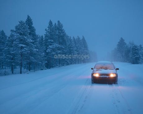 Car on rural road during winter in Dalarna, Swedenの写真素材 [FYI02208992]
