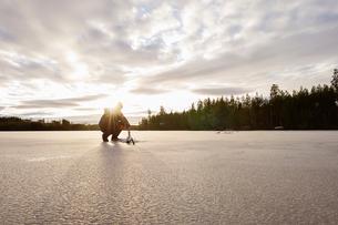 Sweden, Vastmanland, Bergslagen, Hallefors, Natsjon, Man preparing for ice fishing on frozen lakeの写真素材 [FYI02209005]