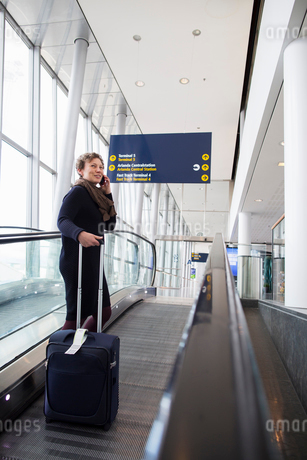 A woman talking on her cell phone in the Stockholm Arlanda Airportの写真素材 [FYI02209010]