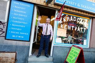 Man waving at door of storefrontの写真素材 [FYI02209021]