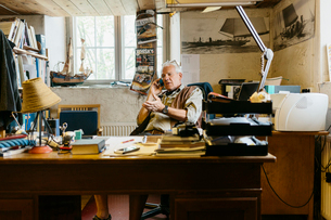 Rope maker talking on his cell phone at his desk in shopの写真素材 [FYI02209022]