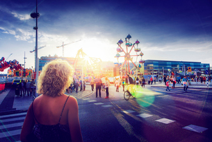 Sweden, Skane, Malmo, Anna Lindhs Plats, Woman crossing city street towards travelling carnival grouの写真素材 [FYI02209050]
