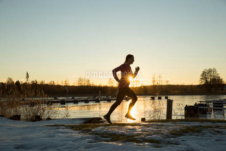 Silhouette of woman jogging by lake at sunsetの写真素材 [FYI02209105]