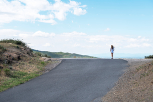 a girl standing on the crest of a rural roadの写真素材 [FYI02209151]