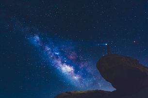 USA, California, Joshua Tree National Park, Man standing on rock and looking at Milky Wayの写真素材 [FYI02209159]