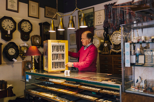 Man at counter in antique store in Swedenの写真素材 [FYI02209160]