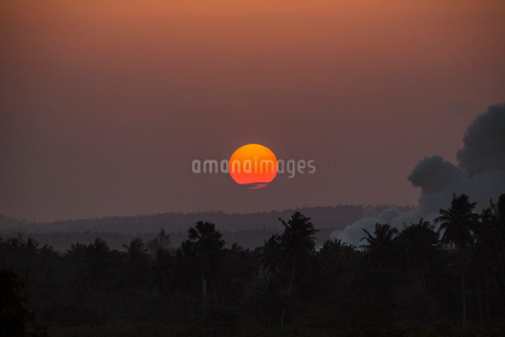 Sunset over trees with smoke in Kenyaの写真素材 [FYI02209165]