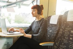 Woman using laptop on trainの写真素材 [FYI02209168]