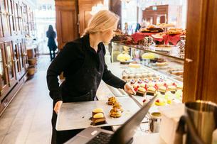 Baker putting baked goods in display window in Swedenの写真素材 [FYI02209176]