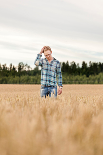 Finland, Uusimaa, Siuntio, Mid adult man standing in wheat fieldの写真素材 [FYI02209190]