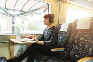Woman using laptop on trainの写真素材 [FYI02209222]