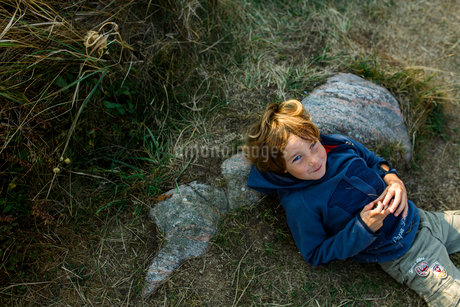 A young boy lying down against a rockの写真素材 [FYI02209226]