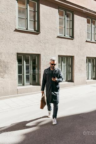 Man walking down street with smart phone in Stockholm, Swedenの写真素材 [FYI02209235]