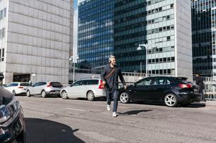 Man running across street in Stockholm, Swedenの写真素材 [FYI02209238]