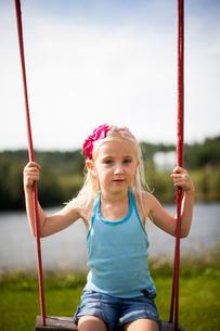 Sweden, Medelpad, Girl (6-7) sitting on rope swingの写真素材 [FYI02209243]