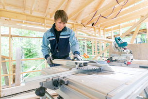 Sweden, Sodermanland, Mid adult man cutting wood with electric sawの写真素材 [FYI02209247]