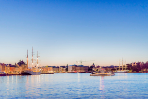 Sweden, Sodermanland, Stockholm, Illuminated city waterfront with ships at sunsetの写真素材 [FYI02209269]