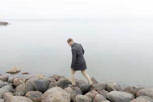 Man on rocky coastline in Smaland, Swedenの写真素材 [FYI02209286]